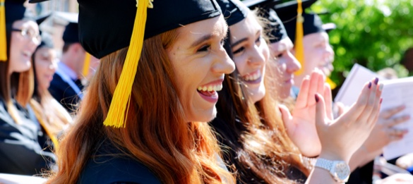 Students at University of the Ozarks graduation ceremony clapping.